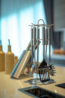 Batería de cocina. conjunto de utensilio de cocina moderno (espátula, batidor y una cuchara ranurada y espagueti