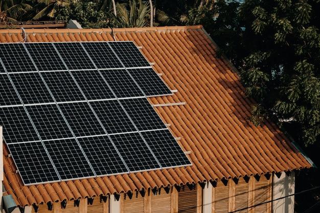 Batería moderna de paneles de energía solar en el techo de la casa