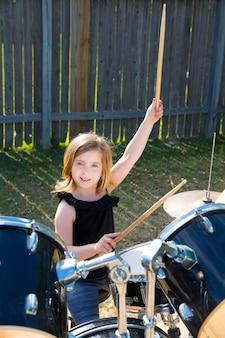 Batería rubia del niño del batería que toca los tambores en el patio trasero de tha