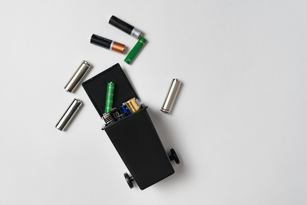 Baterías usadas en el compartimiento en el fondo blanco. contaminación ambiental con residuos tóxicos domésticos