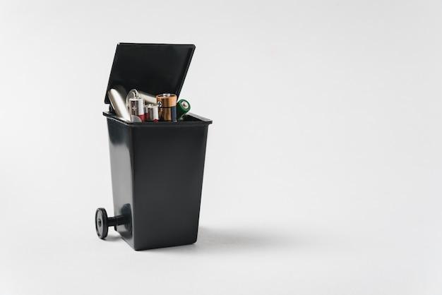 Baterías usadas en el contenedor sobre un fondo blanco. concepto de residuos electrónicos.