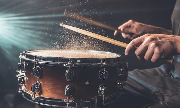 El baterista con baquetas golpeando el tambor con salpicaduras de agua sobre fondo negro bajo iluminación de estudio de cerca.