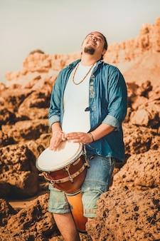 Baterista de boho tocando el tambor en la playa sobre las piedras