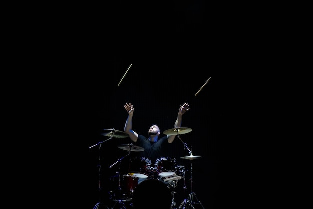 El baterista en una gorra y auriculares toca la batería en un concierto bajo la luz blanca en un humo.