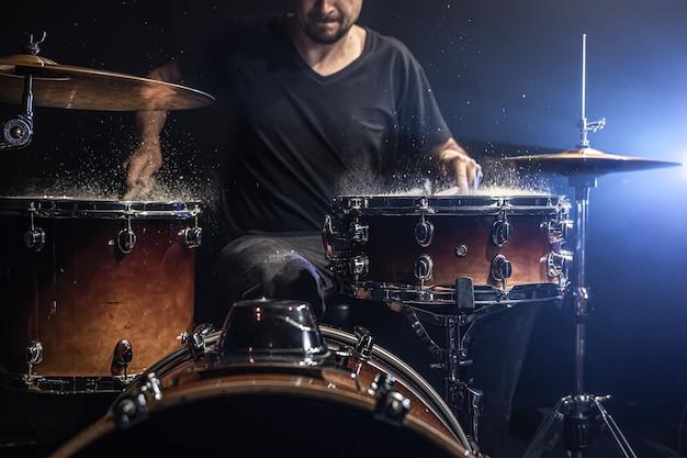 Un baterista masculino toca baquetas en un tambor con salpicaduras de agua en una habitación oscura.