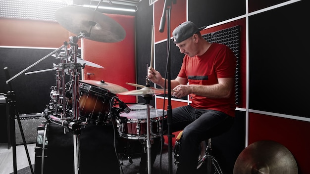 El baterista profesional moderno toca la batería en una base de ensayo, estudio de grabación rojo y negro