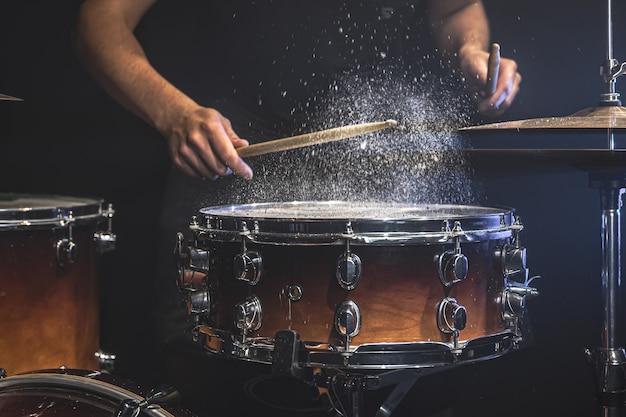 El baterista toca el tambor con salpicaduras de agua.