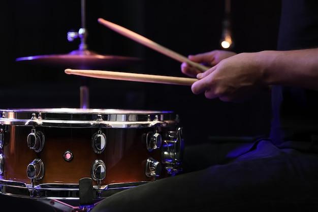 El baterista tocando baquetas en un tambor en la oscuridad. concepto de concierto y actuación en directo.