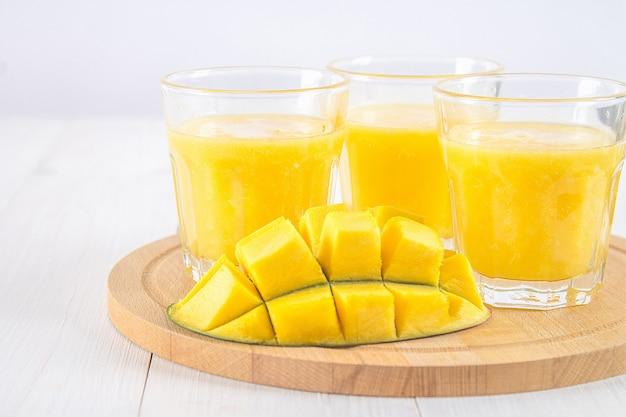 Batido amarillo de mango, plátano y naranja sobre una mesa de madera blanca.