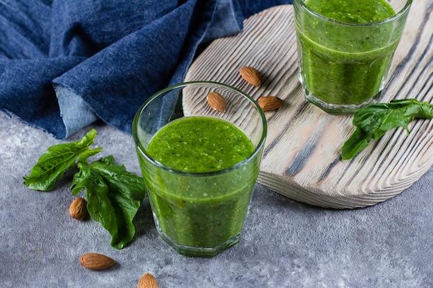 Batido de batido verde con manzana verde, espinaca, kiwi y almendras sobre fondo de concreto gris.