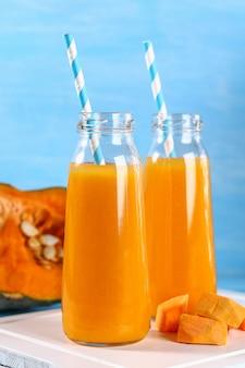 Batido de calabaza embotellado. jugo de la calabaza en una tabla azul. bebidas de otoño.