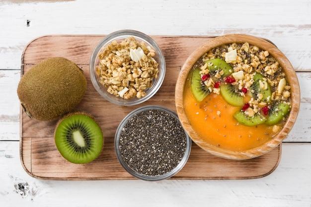 Batido con cereales de frutas y chia en mesa de madera blanca