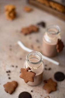 Batido de chocolate en botella de vidrio con galletas desmenuzables de pan de jengibre en la mesa