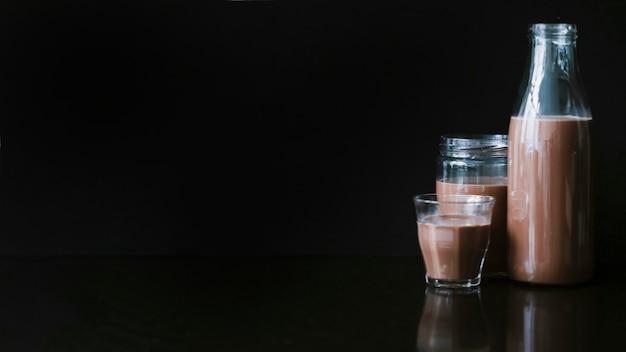 Batido de chocolate en la jarra; vaso y botella sobre fondo negro