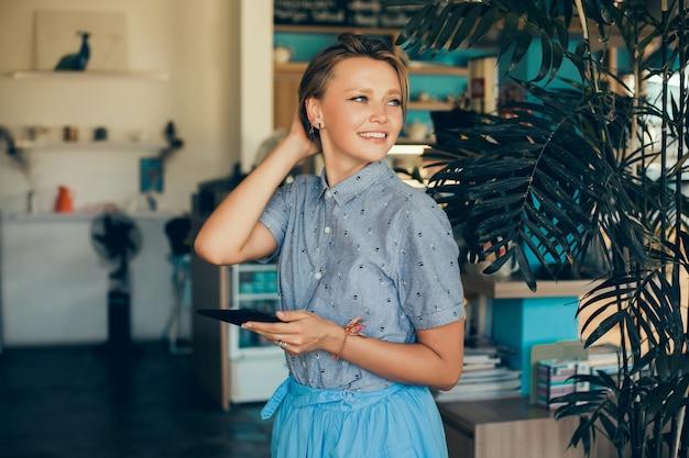 Batido de consumición de la mujer joven en el café, retrato feliz al aire libre