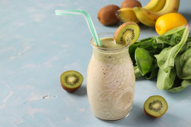 Batido de desintoxicación saludable kiwi, plátano, espinaca y limón en frasco de vidrio sobre fondo azul claro con ingredientes frescos