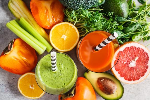 Batido de desintoxicación verde y naranja en vidrio. ingredientes para el fondo de batido de desintoxicación. concepto de comida saludable.