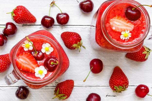 Batido de fresa y cereza en frasco de vidrio con frutas frescas