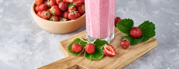 Batido de fresa en un frasco de vidrio y fresas frescas con hojas, pancarta larga