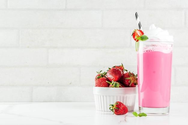 Batido de fresa fría con bayas frescas y menta sobre fondo de mármol blanco