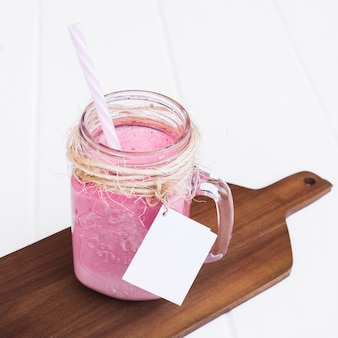 Batido de fresa con paja y etiqueta para maqueta en tablón de madera