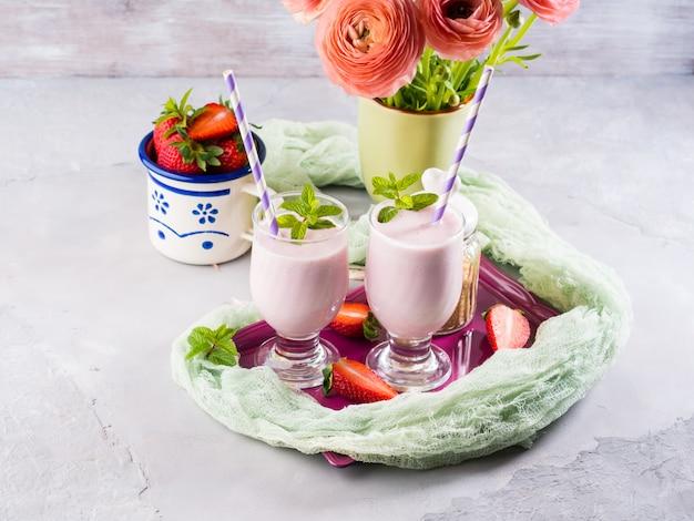 Batido de fresa en vasos para el desayuno romántico de verano saludable. mesa de verano con flores de ranúnculo