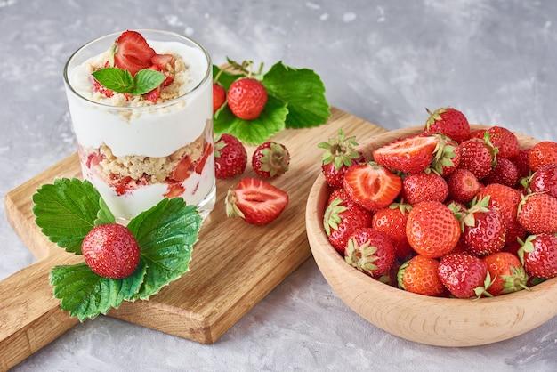 Batido con fresa de verano en frasco de vidrio y bayas frescas en un tazón de madera sobre un fondo gris
