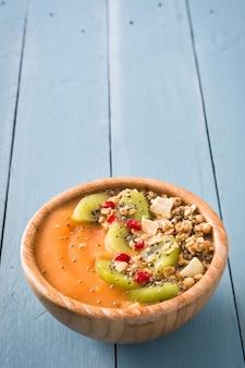 Batido de frutas con cereales y chia en mesa de madera azul