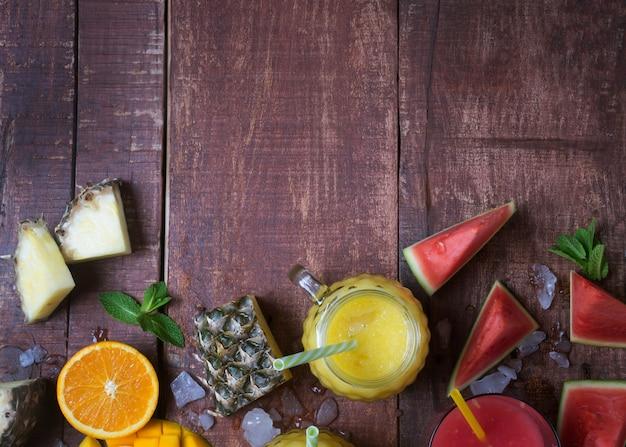 Batido de frutas frescas en un vaso con frutas sobre un fondo rústico de madera marrón, plano