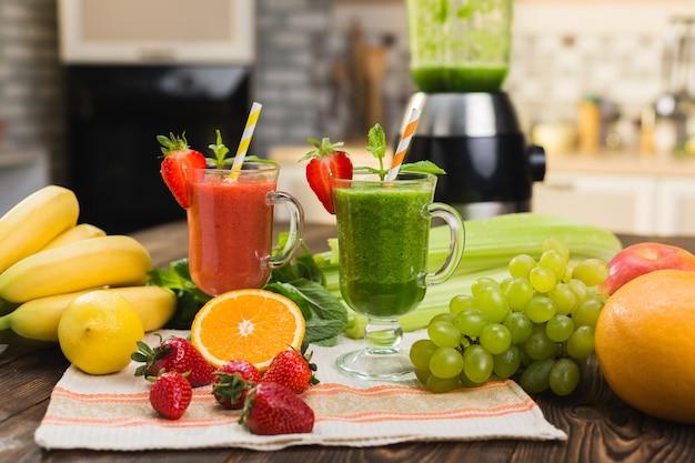 Batido de frutas y verduras frescas en la mesa de la cocina en vidrio