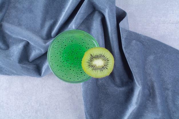 Batido de kiwi fresco saludable en vaso sobre una toalla, sobre la mesa de mármol.