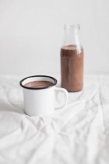 Batido de leche con chocolate en la taza blanca y botella de vidrio en la mesa con tela blanca
