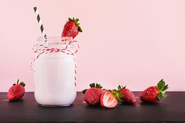 Batido de leche de fresa con baya en tarro de albañil en rosa. de cerca. bebida de verano