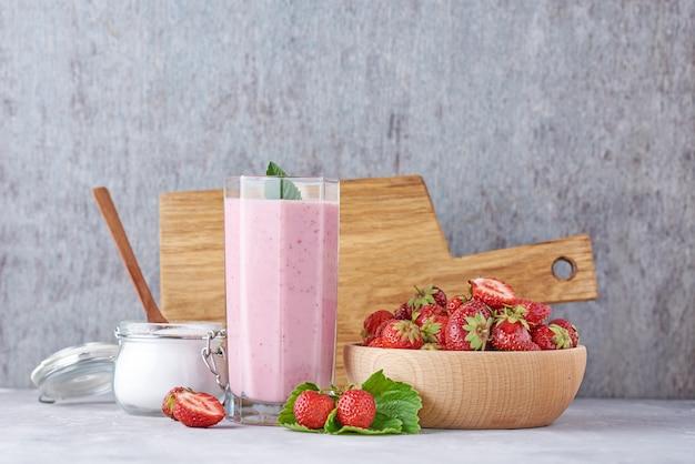 Batido de leche de fresa en un frasco de vidrio y fresas frescas con hojas