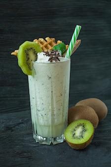 Batido de leche con kiwi, helado y crema batida, malvaviscos, galletas, gofres, servido en un vaso.