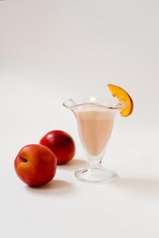 Batido de leche con nectarinas o duraznos frescos en un vaso de vidrio sobre un fondo blanco, junto a duraznos o nectarinas