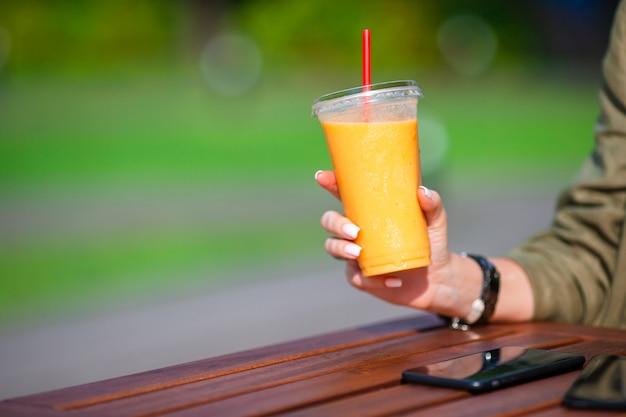 Batido de mango en un vaso en mano femenina de cerca