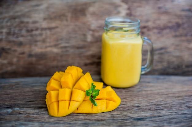 Batido de mango en un vaso mason jarra y mango en el fondo de madera vieja. batido de mango.