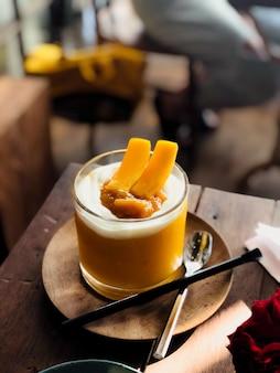 Batido de mango con vidrio hermoso en café moderno.