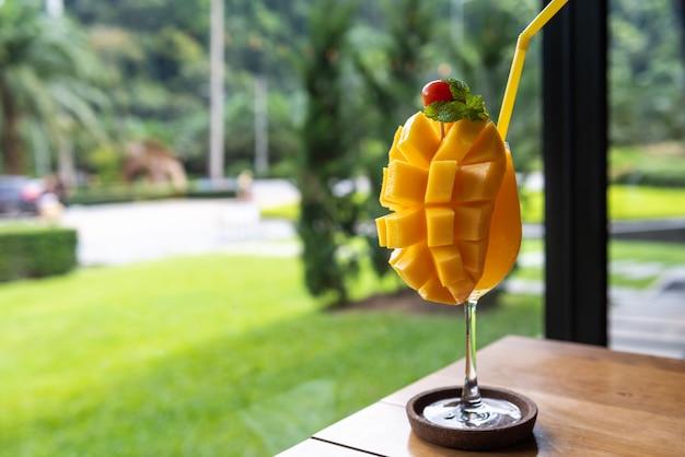 Batido de mango en vidrio sobre mesa de madera