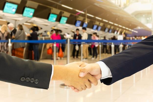 Batido de mano conceptual de viaje de negocios en el aeropuerto con pasajeros en línea de facturación en el aeropuerto