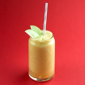 Batido de manzana amarilla fresca y saludable. concepto de dieta de desintoxicación, sobre superficie roja