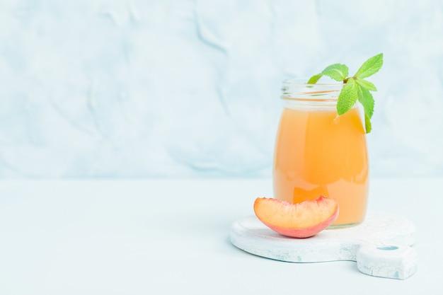 Batido de melocotón en frascos de vidrio con frutas frescas maduras y hojas de menta verde