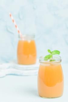 Batido de melocotón en frascos de vidrio con hojas de menta verdes frescas y paja sobre fondo azul pastel
