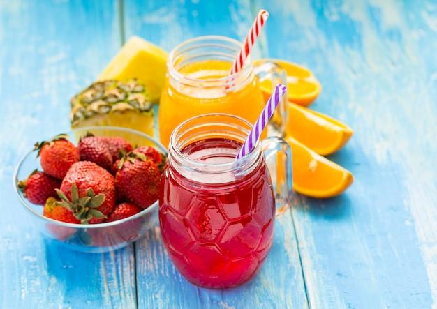 Batido de piña y fresa fresca en vasos con frutas en una pared rústica de madera azul
