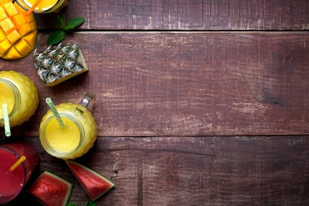 Batido de piña y mango fresco en vasos con frutas sobre un fondo rústico de madera con espacio de copia a la derecha