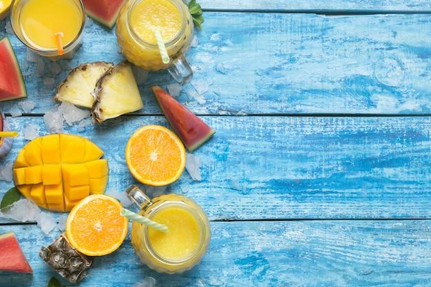 Batido de piña y mango fresco en vasos con pajitas con frutas sobre un fondo rústico de madera azul