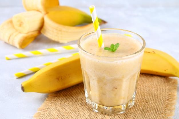 Batido de plátano con tubo de papel y menta. los plátanos son enteros y cortados sobre un fondo gris.