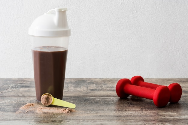 Batido de proteína de chocolate y pesas en la mesa de madera