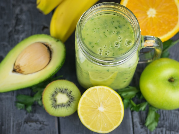 Un batido recién preparado de aguacate, plátano, naranja, limón y kiwi en una mesa de madera. dieta comida vegetariana.